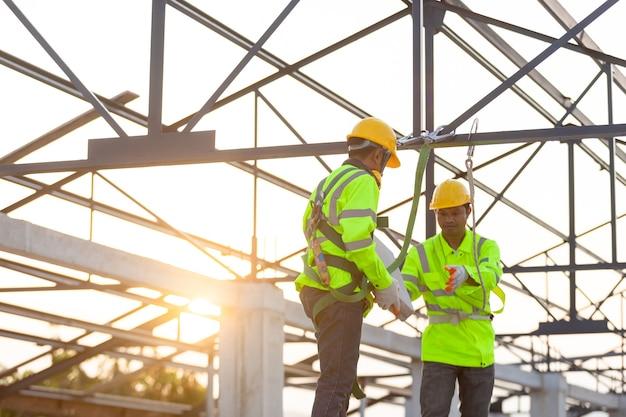 Os trabalhadores asiáticos usam equipamentos de segurança, entregando tijolos uns aos outros. conceito de trabalho em equipe no canteiro de obras.