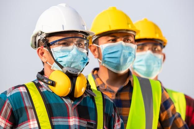 Os trabalhadores asiáticos usam máscaras protetoras para segurança no canteiro de obras. novo normal