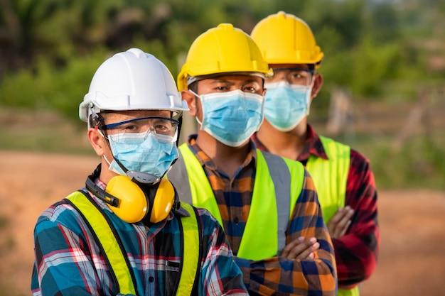 Os trabalhadores asiáticos usam máscaras protetoras para segurança no canteiro de obras.
