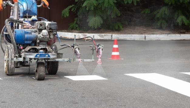 Os trabalhadores da cidade pintam as faixas de pedestres na estrada com uma máquina de pintura.