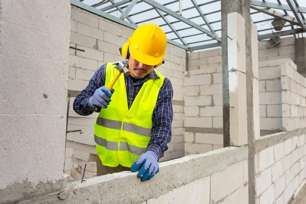 Os trabalhadores da construção civil usam um martelo para martelar um prego de concreto em um bloco de concreto leve para construir uma casa.
