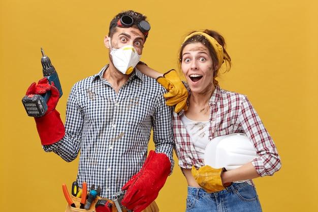 Os trabalhadores da manutenção vestindo roupas casuais segurando equipamentos de construção, surpreendidos por não acreditarem em seus olhos, por terem terminado seu trabalho tão rapidamente. trabalho em equipe e conceito de rapidez