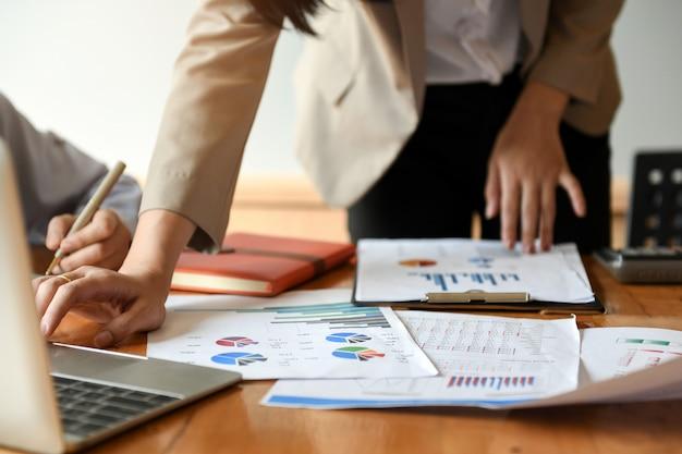 Os trabalhadores de escritório fêmeas estão analisando dados dos gráficos. usam um portátil.