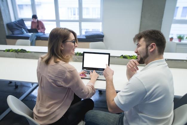 Os trabalhadores de escritório jovem trabalham em um laptop no escritório e sorriem. trabalhar em equipe.