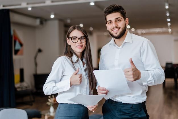 Os trabalhadores de escritório novos homem e mulher mostram os polegares acima
