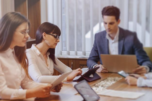 Os trabalhadores de escritório realizam uma reunião em uma mesa para laptops, tablets e papéis, uma grande tv na parede de madeira