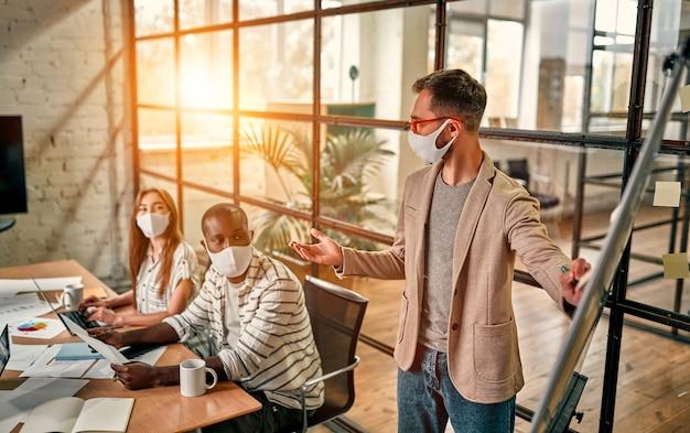 Os trabalhadores discutem e se encontram enquanto usam uma máscara médica para se proteger contra o vírus corona. um jovem escreve um mapa mental em um quadro branco e faz novos planos de negócios durante a pandemia covid-19.