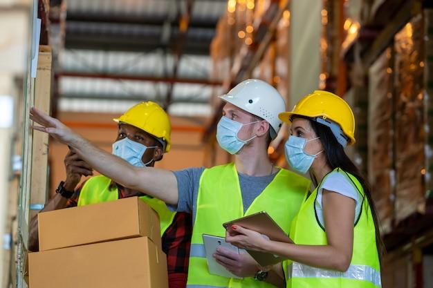 Os trabalhadores do armazém do grupo usando máscara protetora trabalhando juntos no armazém, o coronavirus, se transformaram em uma emergência global.
