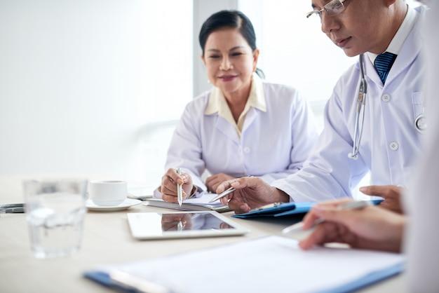 Os trabalhadores do hospital analisando dados médicos em uma reunião