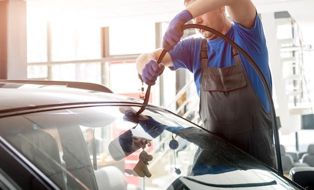 Os trabalhadores especiais de automóveis removem o pára-brisa ou o para-brisa de um carro na garagem da estação de serviço.