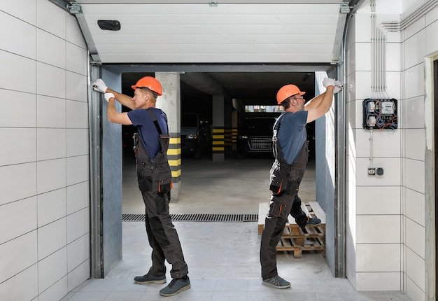 Os trabalhadores estão instalando portões de elevação na garagem.