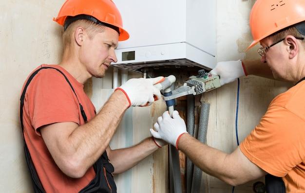 Os trabalhadores estão soldando tubos de plástico e os conectando a uma caldeira a gás doméstica