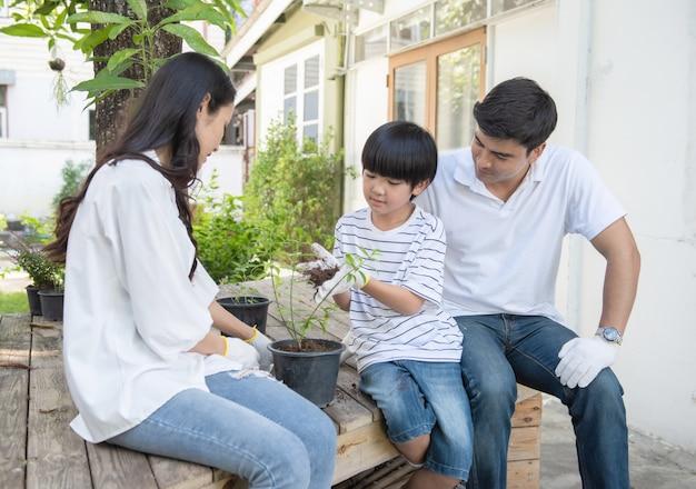 Os trabalhos de equipa do pai caucasiano, da mãe asiática e do filho novo que inclinam-se para plantar a árvore no pote no jardim da frente em casa, a família nova feliz tem o tempo de lazer no fim de semana.