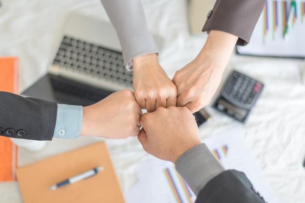 Os trabalhos de equipa juntam-se às mãos, close-up dos sócios comerciais que fazem a pilha das mãos na reunião, conceito do negócio.