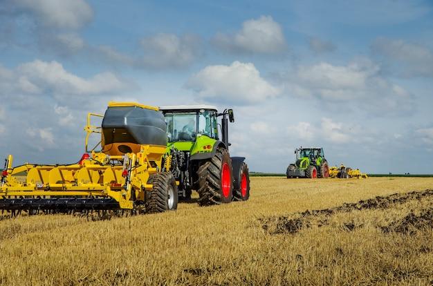 Os tratores trabalham no campo, sistema de preparo do solo com tremonha para fertilizantes no campo