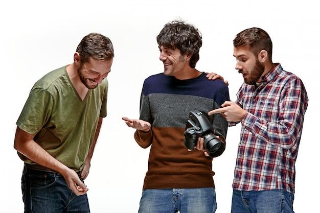 Os três amigos do sexo masculino com câmera em branco