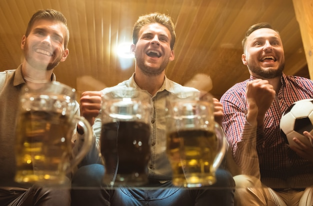 Os três amigos felizes com uma cerveja assistem a uma bola de futebol