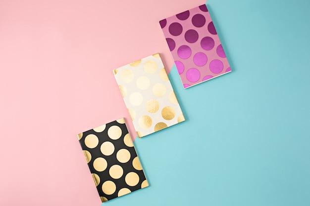 Os três cadernos sobre fundo colorido
