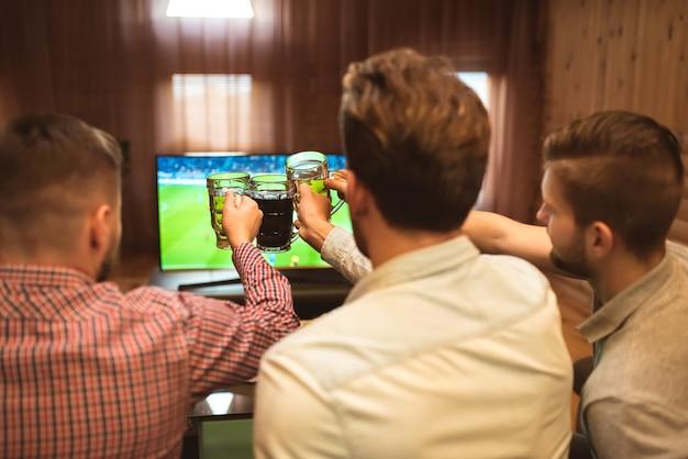 Os três homens assistem a uma bola de futebol e brindam com uma cerveja
