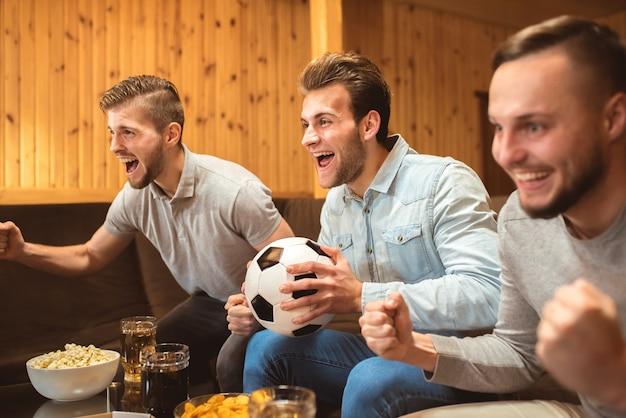 Os três homens com uma cerveja e uma comida assistem a uma bola de futebol e gesticulam
