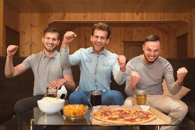 Os três homens da emoção assistem a uma bola de futebol com uma cerveja e uma comida