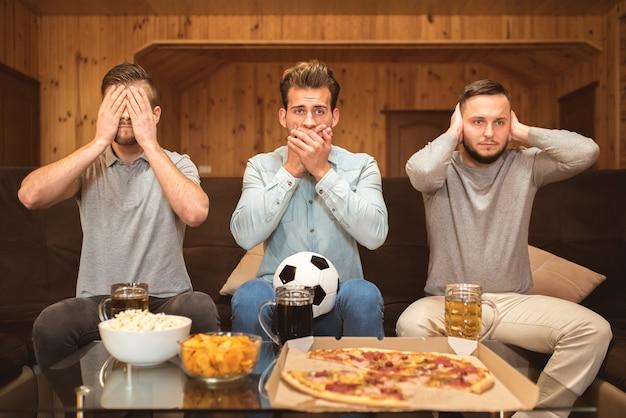 Os três homens gesticulam para perto da mesa com uma comida e uma cerveja