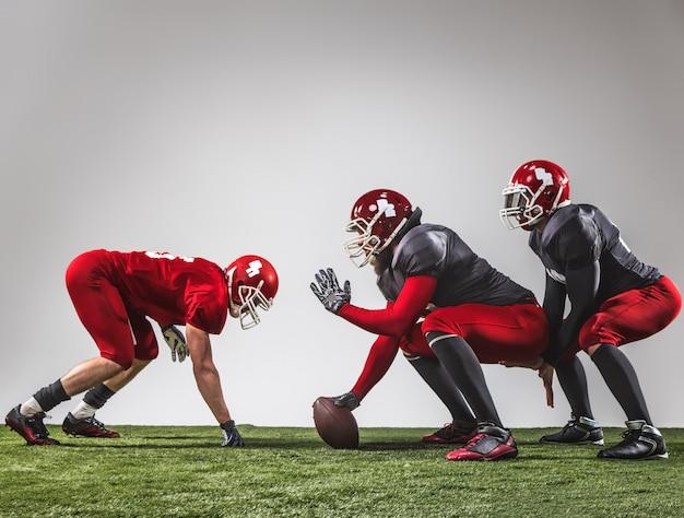 Os três jogadores de futebol americano em ação