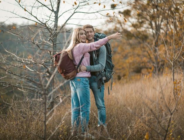 Os turistas admiram a natureza em pé abraçando. foco seletivo em uma encantadora mulher caucasiana com um suéter rosa, apontando a mão para longe. conceito de caminhadas e viagens