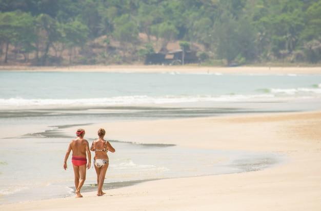 Os turistas andam no mar do fundo da praia na praia de thungwualaen, chumphon, tailândia.