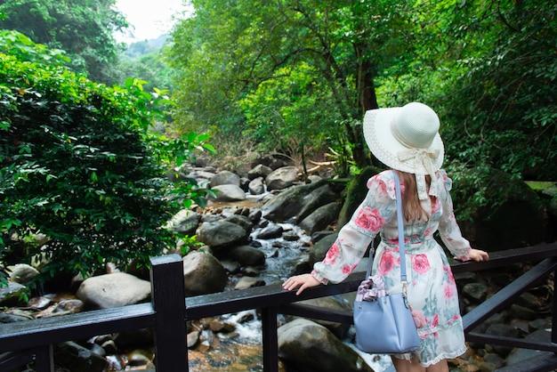 Os turistas asiáticos da menina visitam a beleza da natureza na cachoeira.