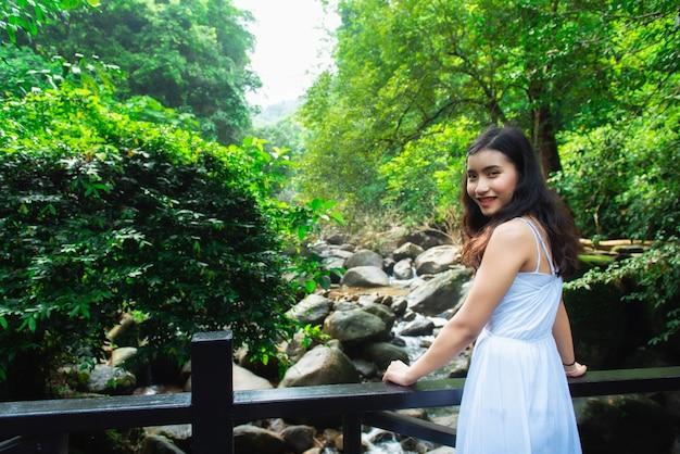 Os turistas asiáticos da menina visitam a beleza da natureza no sinal do parque nacional da cachoeira de phlio em chanthaburi, tailândia.