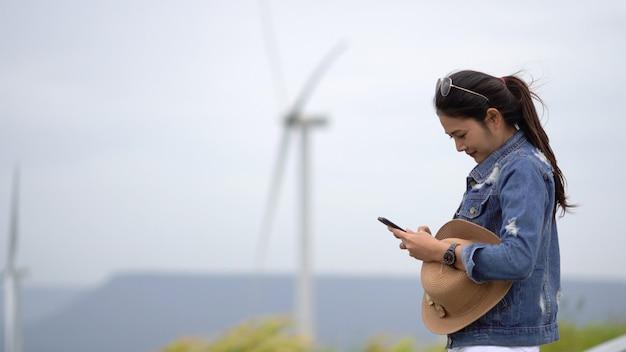 Os turistas asiáticos das mulheres estão tomando um retrato de uma turbina de vento em uma mancha cénico.
