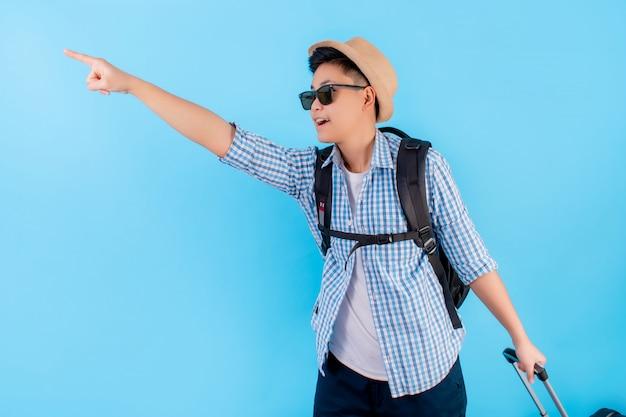 Os turistas asiáticos gostam de apontar para copiar o espaço com a bagagem. sobre um fundo azul e isolado