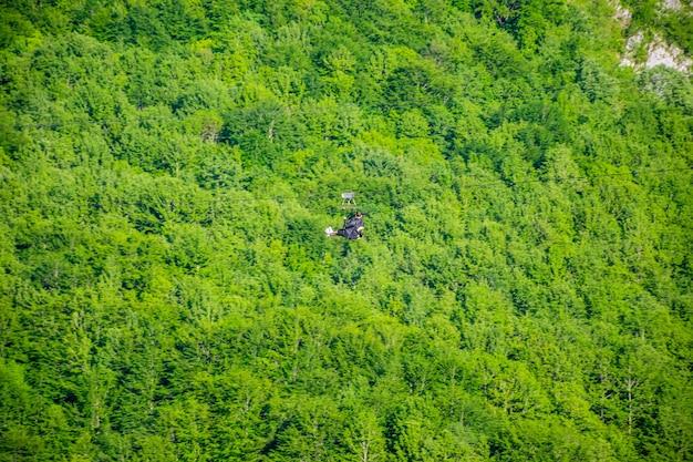 Os turistas cavalgam na tirolesa pelo desfiladeiro do rio tara.
