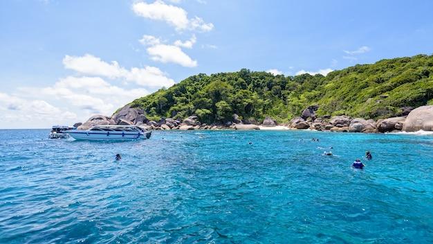 Os turistas desfrutaram de mergulho com snorkel no mar e no céu azul durante o verão na ilha ko ba ngu no parque nacional mu ko similan, província de phang nga, tailândia, tela panorâmica 16: 9