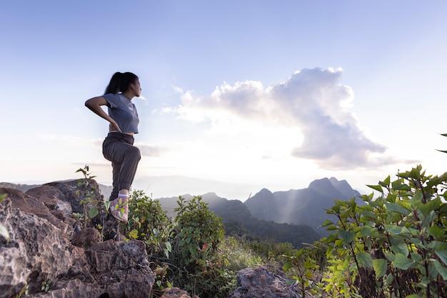 Os turistas estão em pé no topo da montanha.
