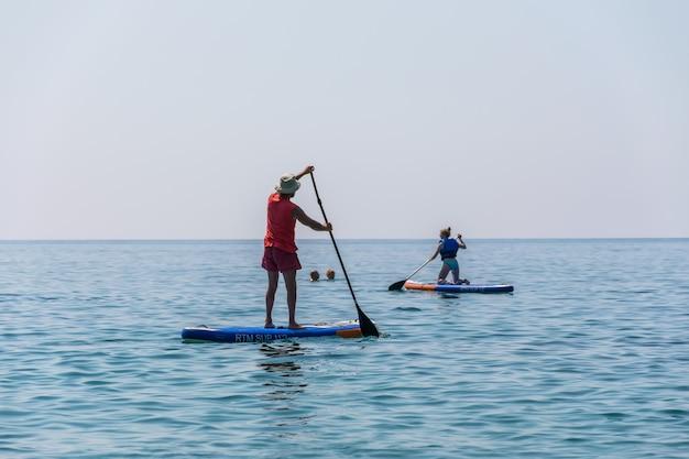 Os turistas estão empenhados em remar no tabuleiro (sup) na superfície do mar calmo.