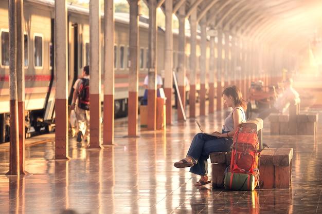 Os turistas estão trabalhando no laptop na estação de trem enquanto esperam pelo trem.