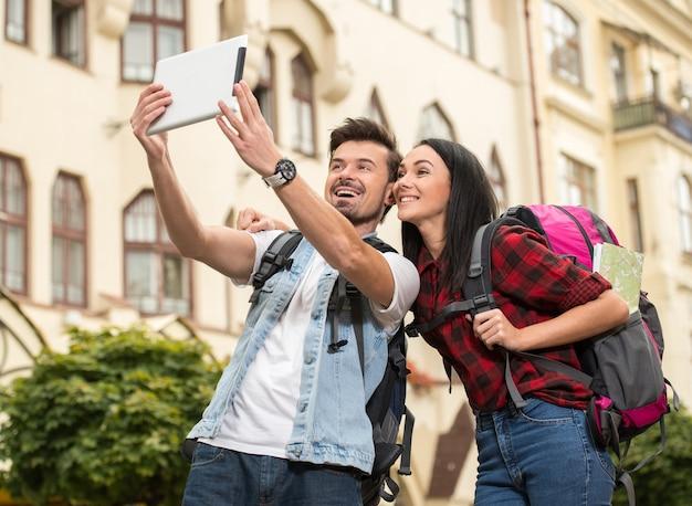 Os turistas felizes estão tomando a foto dse com tabuleta.