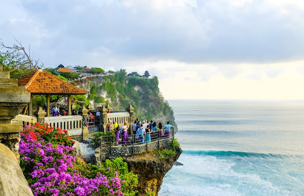Os turistas ficam ao pôr do sol e admiram a paisagem em um penhasco perto do templo de uluwatu, na ilha de bali, indonésia