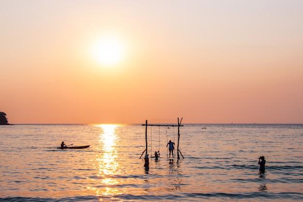 Os turistas jogam no mar da água durante o por do sol na ilha trat kom koh bang do bang do área bao, tailândia.