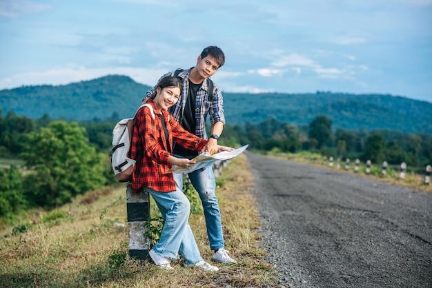 Os turistas masculinos e fêmeas em pé olham para o mapa na estrada.