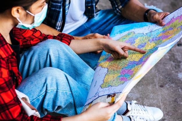 Os turistas masculinos e femininos olham para o mapa ao lado da ferrovia.