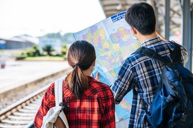 Os turistas masculinos e femininos olham para o mapa ao lado dos trilhos.