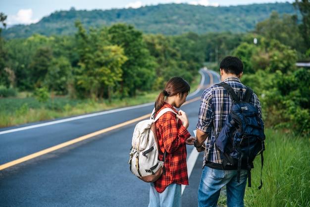 Os turistas masculinos e femininos olham para o mapa na estrada.