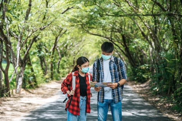 Os turistas masculinos e femininos usam máscaras médicas e olham o mapa na rua.