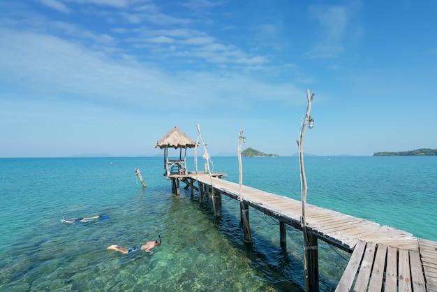 Os turistas mergulham na água de turquesa de cristal perto do recurso tropical em phuket, tailândia.