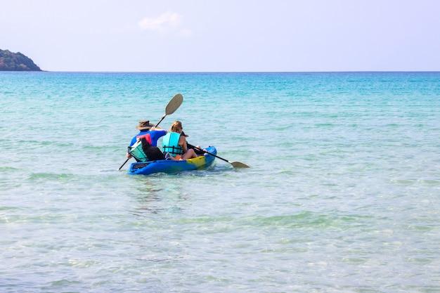 Os turistas que kayaking o bao bonito do estrondo do ao da área do mar na ilha trat de koh kood, tailândia.