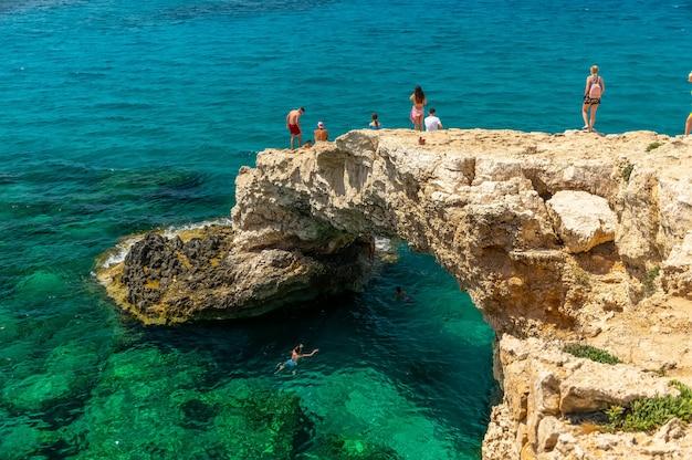 Os turistas saltam de uma altura para as águas azuis do mar mediterrâneo.