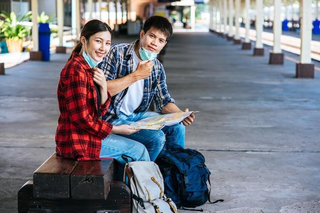 Os turistas, tanto homens quanto mulheres, sentam-se e olham o mapa ao lado da ferrovia.